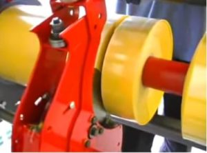yellow material being slitted by band saw